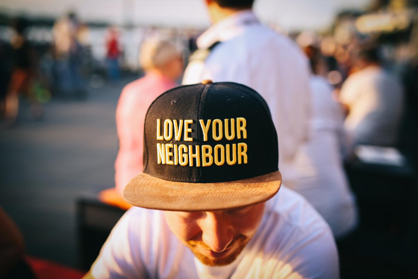 Man med keps med texten Love your neighbour